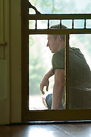 Young man seated on porch viewed through screen door