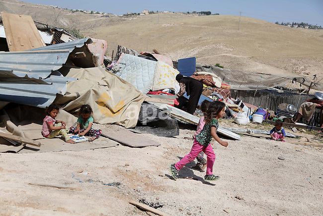 children from the Arab Jahalin Bedouin community play past the debris of homes in the West Bank Bedouin camp of al-Khan al-Ahmar on April 7, 2016 after Israeli authorities demolished four houses that they said were built without permission. Photo by Hamza Shalash