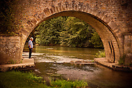 A man stands under an old stone bridge over a river near Monfort, France