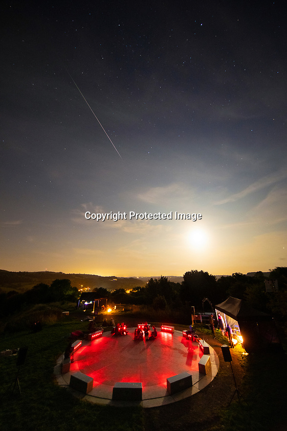 12/08/19<br /> <br /> A shooting star from the Perseid meteor shower strikes a path so dazzling, it can be seen despite a bright moon and a crowd of people illuminated by red lights at the StarDisc overlooking Wirksworth in the Derbyshire Peak District. <br /> <br /> Dozens of star gazers waited late into the evening for clouds to clear while listening to 'Music for Meteors' a performance of ambient music by Gong before this meteor lit up the sky at 20.21.<br /> <br /> StarDisc is a 21st century stone circle and celestial amphitheatre created by Aidan Shingler. It spans 12 meters (40 ft). Carved into black granite is a star chart that mirrors the northern hemisphere's night sky. The surface of the stone circle is inscribed with the constellations, their names, and a depiction of the Milky Way. Contrasting with the star chart is a perimeter of silver granite on which 12 seats are positioned. The seats denote the months of the year.<br /> <br /> The bright Perseids are perhaps the most popular meteor shower of the year, but this year they'll be washed out by a close-to-full moon during their peak. Spectators can expect to see just 10-15 Perseids per hour or maybe slightly more on the peak, which is the night of Aug. 12-13 .<br /> <br /> <br /> All Rights Reserved, F Stop Press Ltd +44 (0)7765 242650 www.fstoppress.com rod@fstoppress.com