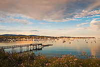 Southwest Harbor, at the mouth of Somes Sound in Acadia National Park, offers a protected haven for a large fleet of pleasure boats and ready access to the Gulf of Maine and the archipelago of islands to the south and west. In this image, the harbor is filled by the late afternoon sun and the vestiges of a recent thunder storm lingering in the sky.