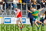 Donal O'Sullivan of Kenmare/Kilgarvan/Dr Crokes gets his effort awas despite the attempted hook from Lixnaw's Shane McElligott in the U21 County Hurling final in Austin Stack Park on Monday.