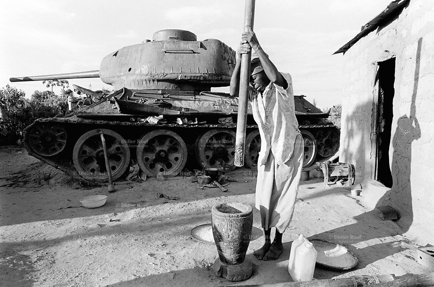 Angola. Province of Cuando Cubango. Menongue. Heavy fightings over the last 25 years of civil war between the Governement and Unita. Old woman crushes corn in front of her house with a destroyed T34/85 tank in her courtyard. © 2000 Didier Ruef