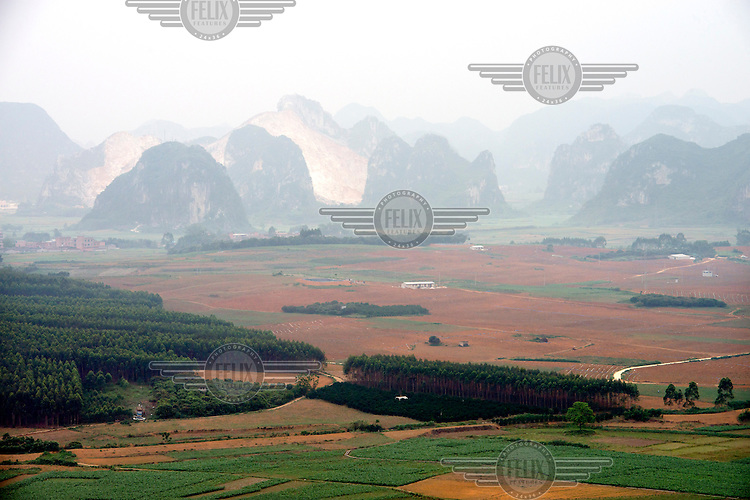 Brown fields surround a small village with limestone karsts rising in the distance. /Felix Features