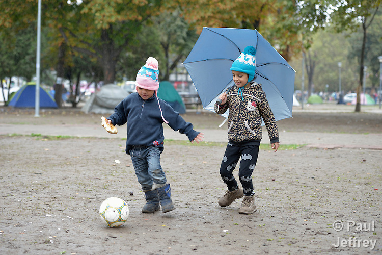 Four-year old Mashad plays football with his 7-year old sister, Farah, in a city park in Belgrade, Serbia. They are refugees from Syria, and with their family fled that nation for western Europe. This park has filled with refugees from several countries stopping over on their way to Germany, Sweden, Holland, and elsewhere. <br /> <br /> Parental consent obtained.