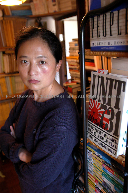 10/24/2002--Himeji, Japan..Wang Xuan poses in her office filed with testimonies and documentation on the activities of Japan's wartime Unit 731, the biological and chemical warfare unit of the Imperial Army that operated in China. Wang Xuan has played a crucial role in getting the witnesses to trial, and collecting detailed evidence for the lawsuits brought against the Japanese government...All photographs ©2003 Stuart Isett.All rights reserved.This image may not be reproduced without expressed written permission from Stuart Isett.