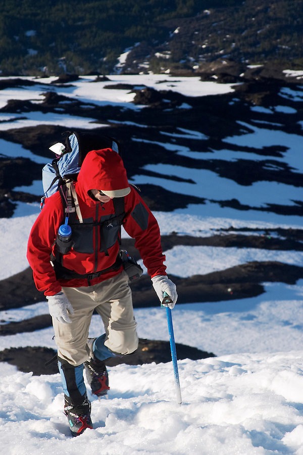 Man in red jacket climbing up snow on Mount Adams, Yakima County, Cascade  Mountains, Washington, USA