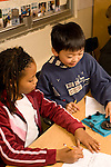 Education elementary Grade 3 science classroom male and female student doing experiment together on velocity vertical