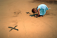 Little girl playing giant tic-tac-toe in the sand