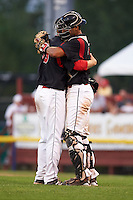 Batavia Muckdogs pitcher Steven Farnworth (55) and catcher Brad Haynal (23) embrace after closing out a game against the West Virginia Black Bears on August 30, 2015 at Dwyer Stadium in Batavia, New York.  Batavia defeated West Virginia 8-5.  (Mike Janes/Four Seam Images)