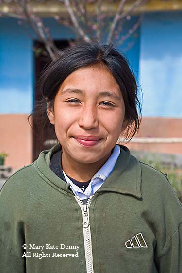 Young girl, nine years old, smiles in front of school in Peru