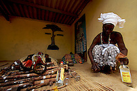 """a """"Trokosi"""" priestess prepares cash and  Gyn  in front of her Gods  while performing a traditional pagan ritual in his shrine  in Kilkor, in the Volta region, Ghana on Friday March 09 2007.."""