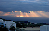 Shafts of sunlight penetrating through early morning cloud over the Canarian countryside and the Atlantic. San Miguel, Tenerife, Canary Islands.