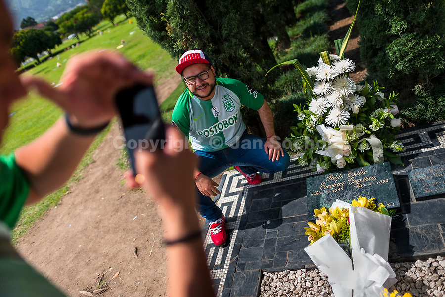 """Young Colombian men take snapshots of themselves while visiting the tomb of the drug lord Pablo Escobar at the cemetery of Montesacro, in Itagüí, Colombia, 2 December 2017. Twenty five years after Pablo Escobar's death, the legacy of the Medellín Cartel leader is alive and flourishing. Although many Colombians who lived through the decades of drug wars, assassinations, kidnappings, reject Pablo Escobar's cult and his celebrity status, there is a significant number of Colombians who admire him, worshipping the questionable """"Robin Hood"""" image he had. Moreover, in the recent years, the popular """"Narcos"""" TV series has inspired thousands of tourists to visit Medellín, creating a booming business for many but causing a controversial rise of narco-tourism."""