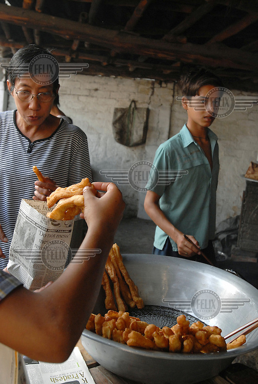 Chinese customers buy Chinese bread sticks fried by an Indian boy on a stall in the market in the Tangra district, which has a large Chinese community. .