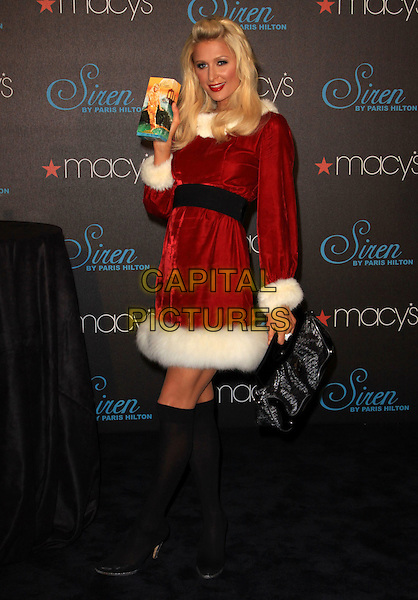 PARIS HILTON .celebrates the launch of her latest fragrance 'Siren' held At Macy's Glendale Galleria, California, USA, .3rd December 2009..full length red christmas santa mrs claus xmas outfit dress white fur fluffy trim black waistband knee high socks shoes holding perfume box silver platform velvet bag .CAP/ADM/KB.©Kevan Brooks/Admedia/Capital Pictures