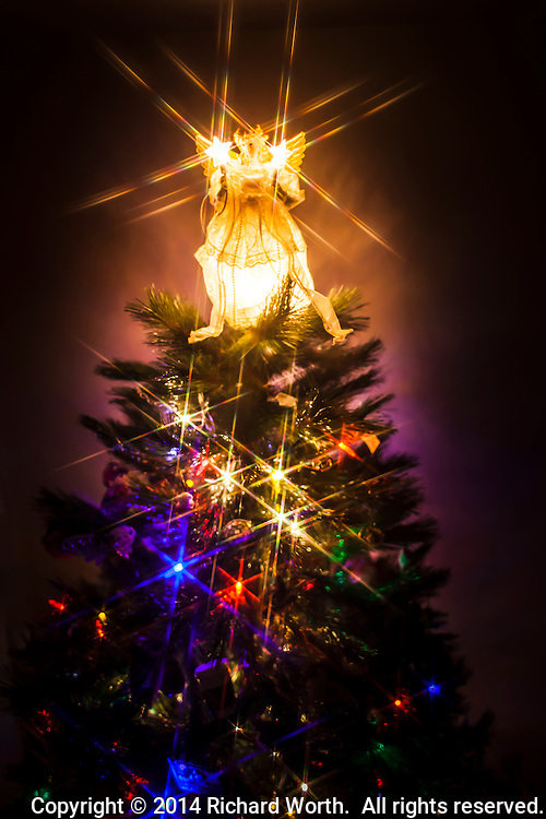 An sparkling angel tops a Christmas tree shining with multicolored lights.