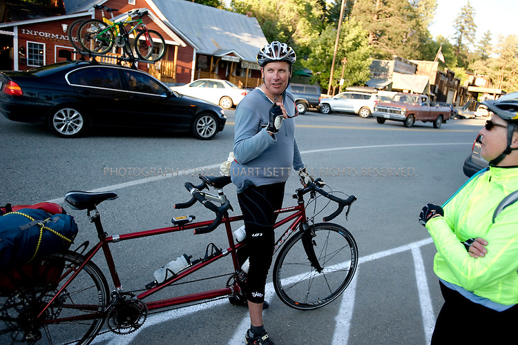 6/11/2008--Winthrop, WA, USA..Cyclists Greg and Caroline Blake stop on Route 20 in Winthrop, WA. Winthrop was officially incorporated on March 12, 1924 and was connected to the West side of the Cascades when Route 20 was finished in 1972. Winthrop is known for the American Old West design of all the buildings in town, making it a popular tourist destination. ..Highway 20, cutting through Washington State's Northern Cascades, is one of the last highways built in the state. The final stretch, connecting the west side to the east sides of the mountains wasn't completed until 1972. the road was one of the of the routes promoted by the Federal Writers Projects guides of the 1930s-1940s. ..©2008 Stuart Isett. All rights reserved.