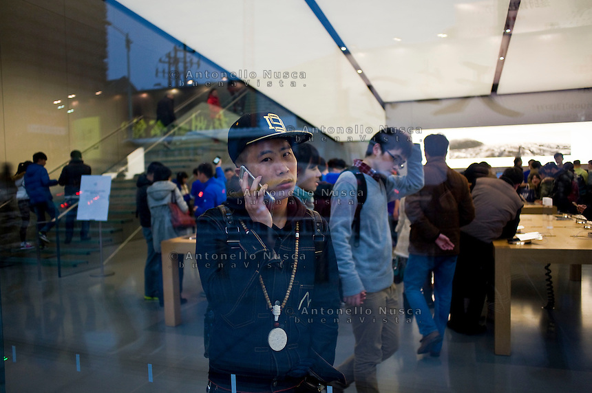 Un ragazzo parla al suo cellulare nel pi&ugrave; grande negozio della Apple in Asia.<br /> A boy talking on his mobile phone in the biggest Apple store in all Asia.