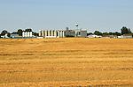 Grain elevators and harvested corn field