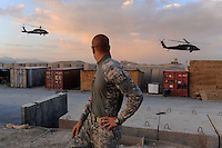 "Pfc. Andrew Petrossian, 20, from Los Angeles, Ca., a refueler with 282nd Aviation Company at FOB Lagman, watches two medical evac Blackhawks take off at sunset, June 22, 2009...""It's awesome,"" he said. ""This is my first month of twelve, and sometimes it's even kinda beautiful and peaceful out here. Sure, it's tiring to work in the sun all day, but you have a real sense of accomplishment - and it's cool to be able to work in aviation."""