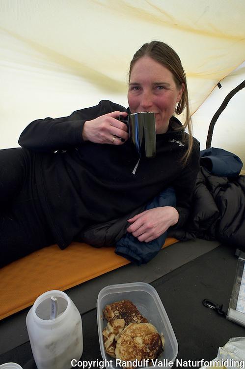 Dame slapper av inne i telt med kaffe og pannekaker. ----- Girl drinking coffe in tent.