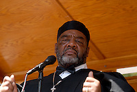 "Bishop C. M. Bailey presides over the mass baptism of the United House of Prayer for All People, a non-denominational Pentecostal church in Harlem in New York on Sunday, August 3, 2008. The church, which has held the baptisms on West 115 street since 1937, uses a fire hose to spray the congregation with city water blessed by the church's bishop. The ceremony is accompanied by music played by several brass ""shout"" bands. (© Richard B. Levine)"