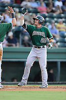 Second baseman Jeremy Sy (20) of the Augusta GreenJackets is congratulated after scoring a run in a game against the Greenville Drive on Friday, July 11, 2014, at Fluor Field at the West End in Greenville, South Carolina. Greenville won, 7-6. (Tom Priddy/Four Seam Images)