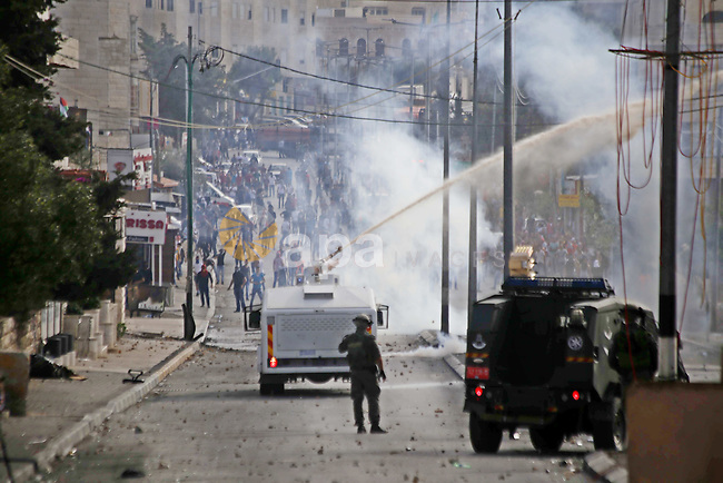 An Israeli military vehicle sprays foul smelling skunk water at Palestinian protesters during clashes in the West Bank city of Bethlehem, on October 13, 2015. A wave of stabbings that hit Israel, Jerusalem and the West Bank this month along with violent protests in annexed east Jerusalem and the occupied West Bank, has led to warnings that a full-scale Palestinian uprising, or third intifada, could erupt. The unrest has also spread to the Gaza Strip, with clashes along the border in recent days leaving nine Palestinians dead from Israeli fire. Photo by Muhesen Amren