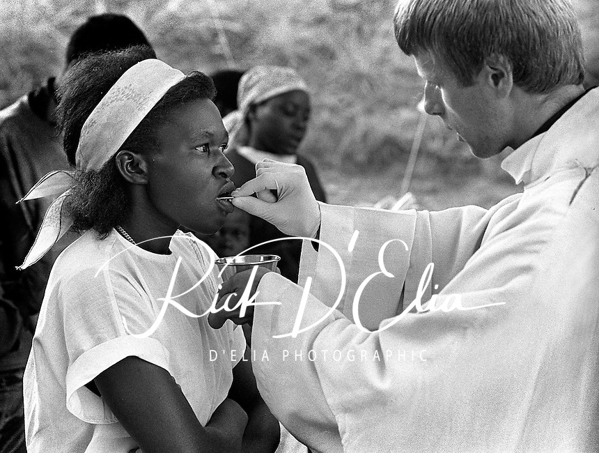 Father Philippe Marie Meuret of the Fraternite de Norte Dame order gives communion to a Rwandan woman in a makeshift chapel on the compound the AmeriCares clinic in Buranga, Rwanda, October 1994. The New Canaan Connecticut humanitarian organization set up their clinic on the road between Goma, Zaire (now Congo) and Kigali, Rwanda to help refugees returning from the camps in Goma and the people living in the area whose illnesses resulted from the destruction of what little infracstracture existed before civil war. (photo Rick D'Elia)
