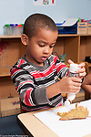 Education preschool 3-4 year olds art activity boy squeezing glue bottle before gluing leaf to paper