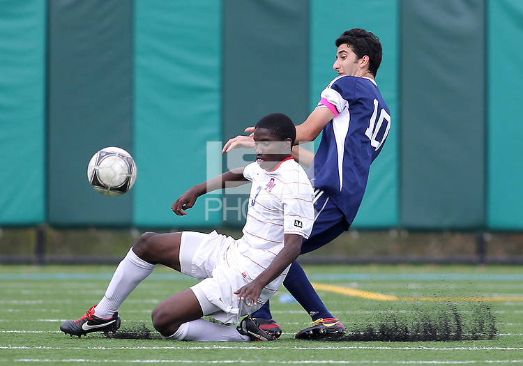 HYATTSVILLE, MD - OCTOBER 26, 2012:  William Kerr (3) of DeMatha Catholic High School slides in front of Arjan Ganji (10) of St. Albans during a match at Heurich Field in Hyattsville, MD. on October 26. DeMatha won 2-0.