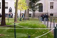 People stand around the John Harvard statue outside University Hall in Harvard Yard at Harvard University in Cambridge, Massachusetts, USA, on Mon., Oct 15, 2018.