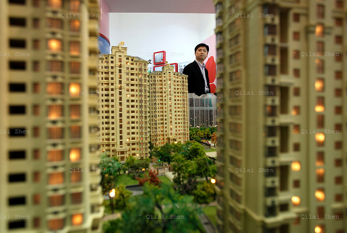 A man looks at models of apartments at a real estate fair in Shanghai, China on 15 March, 2009. For the past decade, Shanghai has underwent the largest reconstruction in recorded history, over 20 million square meters of land, approximately a third of Manhattan, were developed between year 200 and 2005 alone. Despite that however, housing prices have seen a rapid increase, putting the prospect of owning a decent sized home out of the reach of ordinary Chinese citizens, especially middle to low income families.