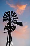 Metal windmill silhouette with pink clouds at sunset, Texas.