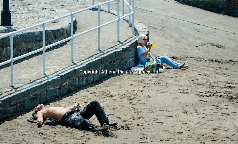 HOT WEATHER WALES Aberystwyth, Ceredigion, West Wales. UK Weather Wednesday  8th June 2016: With yellow warnings for rain across swathes of England the sun comes out at lunchtime with temperatures reaching 19 degrees Celsius after a dull morning. Two people a man and a woman sunbath on the beach during their lunch hour.