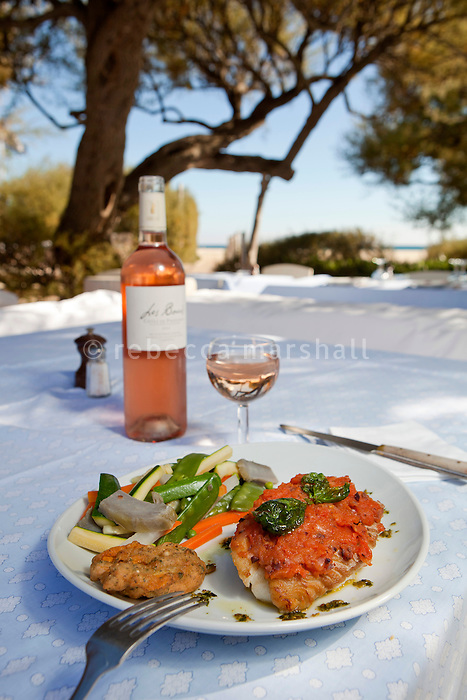 Freshly-caught cod served with a tomato coulis and seasonal vegetables at Club 55 on Pampelonne Beach, Ramatuelle, near Saint Tropez, France, 16 October 2013. The owner of Club 55, Patrice De Colmont, owns an organic farm nearby which produces wine for the restaurant, seen here.