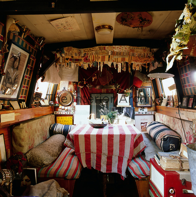 The dining area is situated at the rear of the houseboat and consists of a table flanked by a pair of benches covered in striped and floral fabric