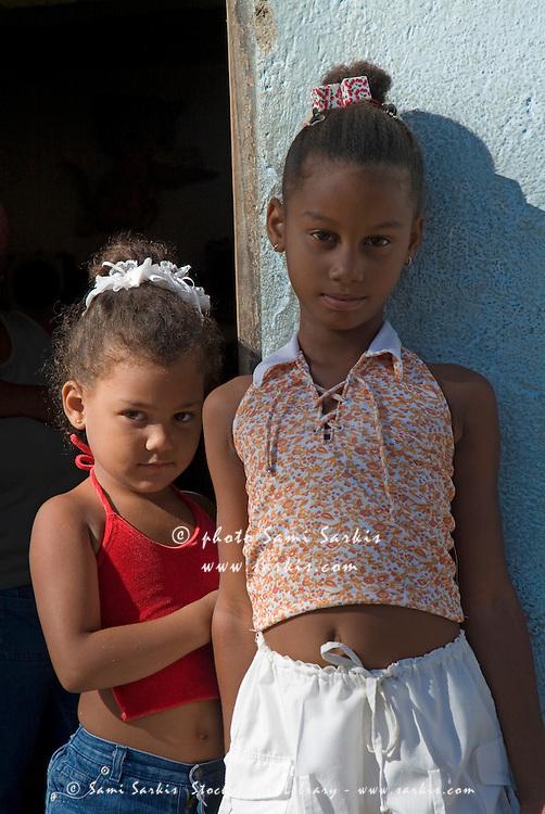 Portrait of two little girls posing on their doorstep, Trinidad, Sancti Spiritus, Cuba.
