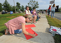 NWA Democrat-Gazette/ANDY SHUPE<br /> Cathy Mathews of Springdale uses a marker Saturday, Aug. 22, 2015, to make a sign as nearly 200 people gathered to protest in front of the Planned Parenthood office 3729 N Crossover Road in Fayetteville. The protest was a part of a national effort to call for the defunding of the organization.