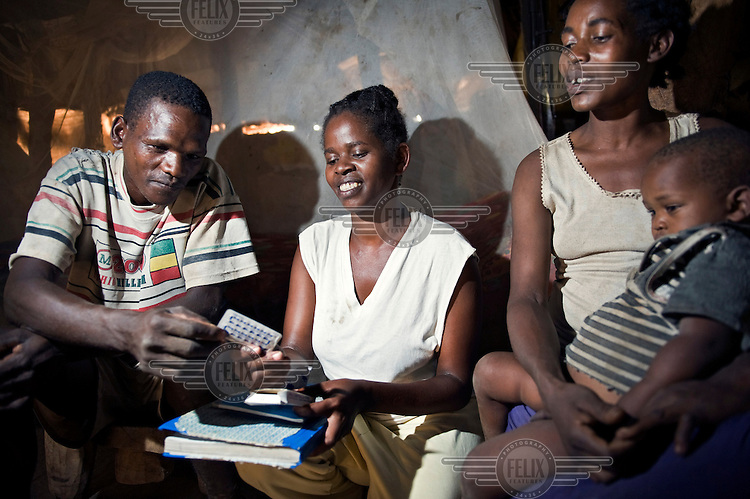 Almaz Dalsha (centre), a health worker, shows a pack of contraceptive pills to Dawalo Dawicho and her husband during a home visit to discuss family planning.