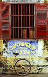 Bicycle 04 - Old weathered Savonnerie Xuong Lam Xa Phong sign, and a yellow bicycle, in Nguyen Thai Hoc St, Hoi An, Viet Nam