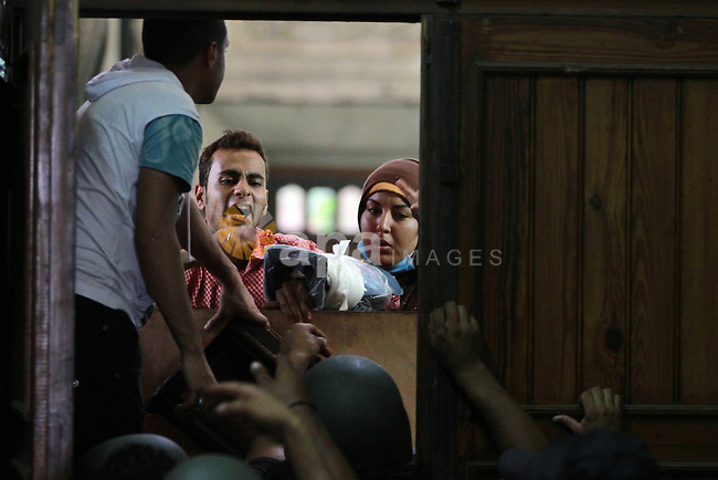 Supporters of deposed Egyptian President Mohamed Mursi talk with media and police from behind their barricade inside the al-Fath mosque in Cairo August 17, 2013. Gunmen opened fire on security forces from a second floor window in al-Fath mosque, where hundreds of Mursi supporters have been taking refuge since protests turned violent on Friday. Photo by Ahmed Asad