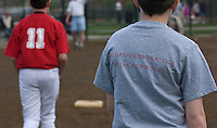 Young boy wears t-shirt with slogan for success during summer baseball league