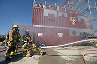 NWA Democrat-Gazette/ANDY SHUPE<br /> Fire captains, firefighters and training officers test a charged line Wednesday, March 7, 2018, during a training workshop for fire department leadership to meet current National Fire Protection Association standards at the Fayetteville Fire Department training facility in south Fayetteville. Thirty students and instructors from agencies in seven states attended the training meant to train department training officers at current standards.