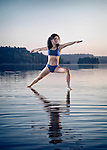 Young woman practicing Hatha yoga on a floating platform in water on the lake in early morning. Yoga Warrior pose, Veerabhadrasana. Muskoka, Ontario, Canada.