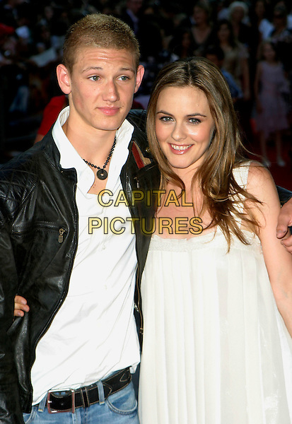 "ALEX PETTYFER & ALICIA SILVERSTONE.Arrivals - World Premiere of ""Stormbreaker"",.Vue West End, Leicester Square, London,.England, July 17th 2006..half length white shimmery dress puffy skirt tulip hem wide straps .REf: AH.www.capitalpictures.com.sales@capitalpictures.com.©Adam Houghton/Capital Pictures."