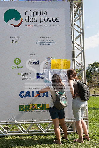Two visitors try to find their way around the People's Summit site with the help of a map taped to a Cupula dos Povos banner. United Nations Conference on Sustainable Development (Rio+20), Rio de Janeiro, Brazil, 15th June 2012. Photo © Sue Cunningham.