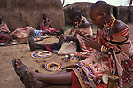 Maasai women making traditional  crafts in a cultural  manyatta  set up for tourists on the edge of the Maasai mara game park.