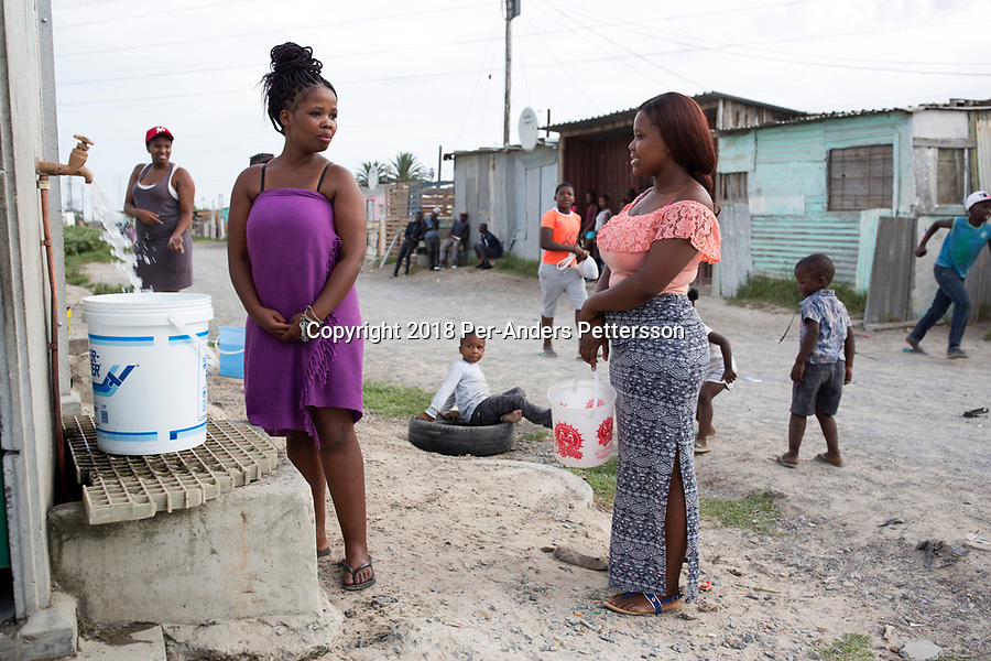 KHAYELITSHA, SOUTH AFRICA – FEBRUARY 8: Women fetch water at a communal tap on February 8, 2018 in Khayelitsha, about 40 kilometers outside of Cape Town, South Africa. The city of Cape Town is experiencing a shortage of water and water restrictions are in place. The big users of water are not the poor in the townships but the wealthy people in the suburbs, who have pools and gardens. (Photo by Per-Anders Pettersson)